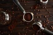 Portafiltry mezi skleněnou sklenicí a gejzír kávy na tmavém dřevěném povrchu