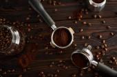Portafilters between glass jar and geyser coffee maker on dark wooden surface