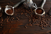Photo Geyser coffee maker with portafilters on dark brown wooden surface with coffee beans