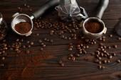 Gejzer kávéfőző portafilters a sötét barna fa felületén kávébab