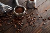 Geyser coffee maker near portafilter on dark brown wooden surface with coffee beans