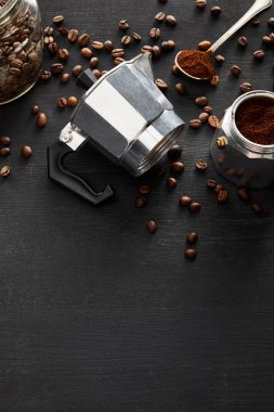 Separated parts of geyser coffee maker near glass jar and spoon on dark wooden surface with coffee beans