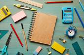 top view of blank brown notebook near school supplies at wooden table