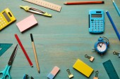 top view of school supplies at wooden table with copy space