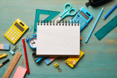 top view of blank notebook near school supplies at turquoise wooden table
