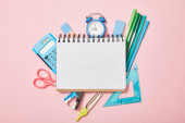 top view of school supplies near blank notebook isolated on pink