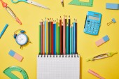top view of colored pencils blank notebook among school supplies on yellow