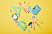 Photo top view of school supplies scattered on yellow background