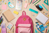 top view of various school supplies with pink backpack on wooden desk