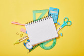 top view of school supplies scattered on yellow background with blank notebook