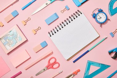 Flat lay with blue and pink school supplies and blank notebook isolated on pink stock vector