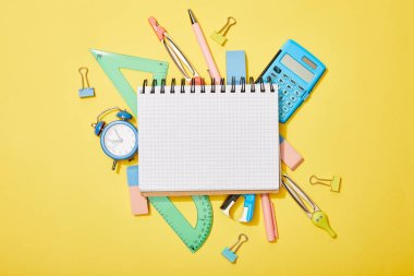 top view of school supplies scattered on yellow background with empty notebook