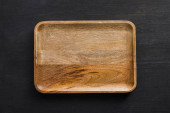 Top view of brown wooden empty dish on dark surface