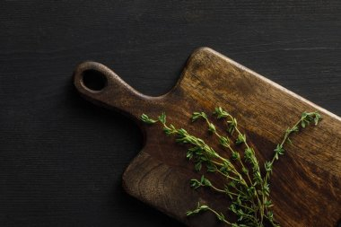 Top view of brown wooden cutting board with thyme twigs on dark surface