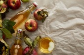 top view of bottles and glass with cider near scattered apples with copy space
