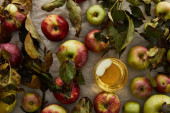 top view of glass with cider near scattered apples