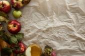 pohled na jablka s listy a skleněnými moštu na pergamenový papír s prostorem pro kopírování