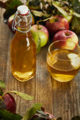 bottle of fresh cider near glass and apples on wooden surface