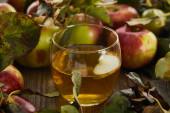 sklenice čerstvého moštu v blízkosti jablek na dřevěném povrchu