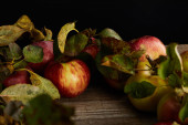 fresh ripe apples and leaves on wooden surface isolated on black