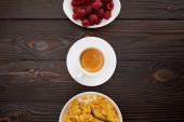 pohled na misku s kukuřičných vločkami a mlékem blízko šálku kávy a plech z malin na dřevěné ploše