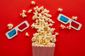 top view of delicious popcorn scattered on red background with 3d glasses