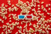 a 3D szemüvegek felülnézete a szétszórt pattogatott kukoricán vörös alapon