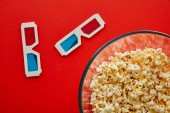 top view of delicious popcorn in bowl near 3d glasses isolated on red