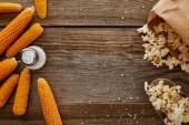 Nejlepší pohled na výtečný popkorn a kukuřici se solí na dřevěném pozadí