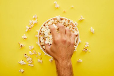 Cropped view of man grabbing delicious popcorn from bucket on yellow background stock vector