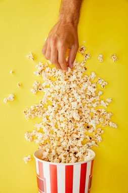 Cropped view of man taking delicious popcorn from bucket on yellow background stock vector
