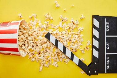 Top view of delicious popcorn scattered on yellow background with clapper board stock vector