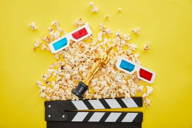 KYIV, UKRAINE - AUGUST 13, 2019: top view of delicious popcorn, 3d glasses and clapper board with golden Oscar statuette on yellow background stock vector