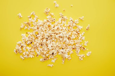Top view of tasty popcorn scattered on yellow background stock vector