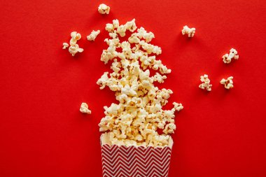 top view of delicious popcorn scattered on red background