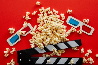 Top view of delicious popcorn near clapper board and 3d glasses on red background stock vector