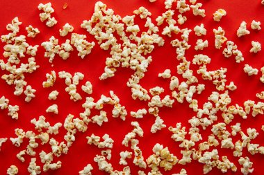 top view of fresh popcorn scattered on red background