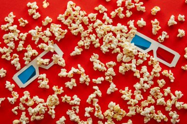 Top view of 3d glasses on delicious scattered popcorn on red background stock vector