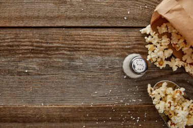 top view of delicious popcorn with salt on wooden background