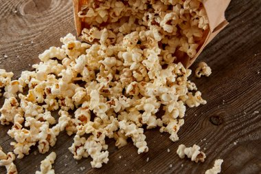 delicious crispy popcorn scattered from paper bag on wooden background