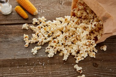 salty delicious popcorn scattered from paper bag near corn on wooden background