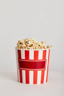 delicious popcorn in red striped paper bucket isolated on grey