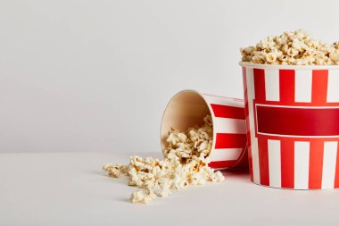 Delicious popcorn scattered from red striped paper buckets isolated on grey stock vector