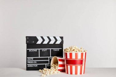Popcorn in striped buckets near clapper board isolated on grey stock vector
