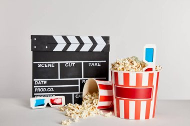 Delicious popcorn scattered from buckets with clapper board and 3d glasses isolated on grey stock vector