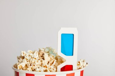 tasty fresh popcorn in paper bucket with 3d glasses isolated on grey