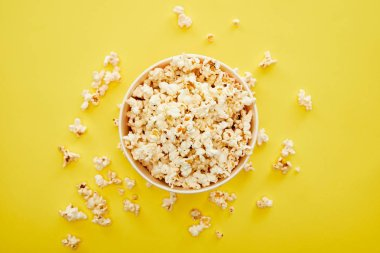 top view of fresh popcorn in bucket on yellow background