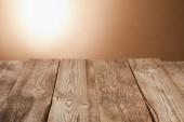 prázdný dřevěný stůl na hnědém pozadí s baterkou