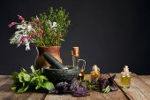grey mortar near clay vase with herbs and small bottles on wooden table isolated on black