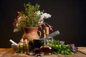 agyag váza, friss fűszernövények és virágok közelében habarcs és zúzás és palackok fából készült asztal izolált fekete